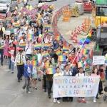 虹色のプラカードを掲げながら行進する「東京ラブパレード」の参加者ら=東京都新宿区で2018年10月8日午後3時54分