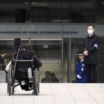 障害者を対象とした初の国家公務員試験の会場に車いすで向かう人=3日午前、大阪市の大阪中之島合同庁舎 (共同通信)